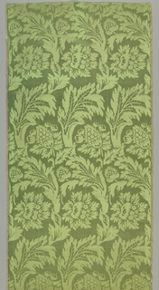 Apple-green satin damask woven with feathery serrated leaves forming parallel serpentine trails from which spring peonies and other blossoms in lateral rows. Striped pink and yellow selvages.