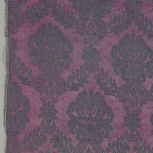 Vertically symmetrical pattern of offset plant motifs set in an ogee grid. Background; red-purple. Pattern; dull blue.
