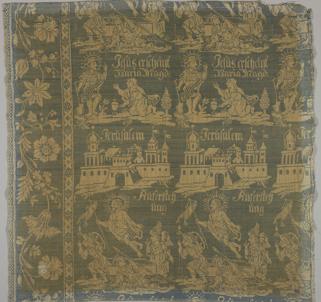 """White linen warp and blue linen weft form a reversible textile. At left and bottom of Component A and left of Component B is a broad, large-scale floral serpentine border. Central portion has repeat of three horizontal rows of design. At bottom: Christ rising from the tomb with the inscription, """"Auferstehung."""" Middle row: a group of buildings with the inscription: """"Jerüsalem."""" Third row: Jesus appearing to Mary Magdalene with the inscription: """"Jesus erscheint Maria Magd."""""""