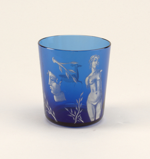 Thin, blue, mouth-blown crystal with white enamel painting of a nude female sculpture, a bust, and laurel leaves.