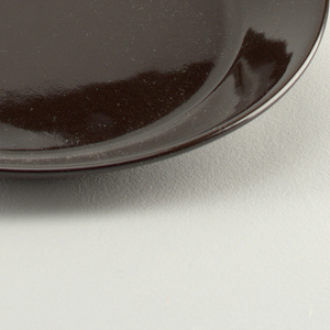 Circular, molded plate. Flat with angled flared rim. Glazed overall with gloss black. Foot ring on underside unglazed.
