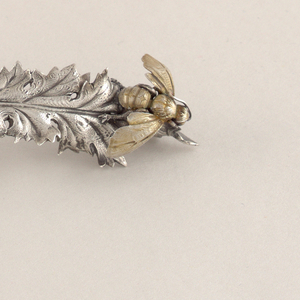 Handle in the form of a gilded honeybee on the end of a leaf.