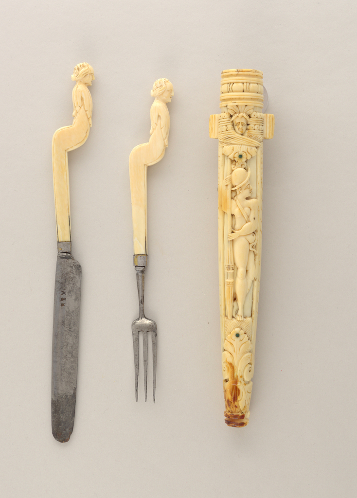 Elaborately carved ivory sheath for two implements. On front a crowned man (King David) playing a harp, on the back a nude female warrior (Minerva) with a helmet and a spear. Sheath is decorated with carved foliage, scrolls and faces on front and back. Two small ribbed tubes on the sides to attach a cord.