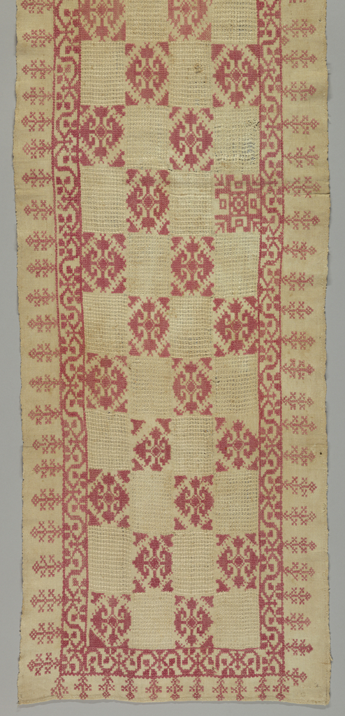 Long rectangular tablecover in natural linen with checkerboard rectangles of openwork; each rectangle is 6 x 9 cm. The alternate checkerboard rectangles are embroidered in red with geometric floral forms. Outer edge has a narrow floral vine border with pendant flowers.