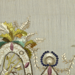 Part of a multicolored border with a main section of repeating triangles and arches. The arches frame a landscape of grass and trees, and the main triangle supports an oval medallion framing Cupid. Probably part of a border for a dress.