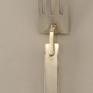 Four-tined fork with flat untensil end attached to flat handle by a trapezoid perpendicular to both. Ovoid terminal.