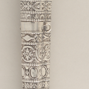 Tapered case for two implements. Stamped horizontal bands with decorative pattern of scrolls, fleur-de-lis, lozenges and rosettes. Segmented beaded borders. Two attachment rings on the sides. Plain end with pointed finial.  Stamped silver cap slides on to sheath (1985-103-43-a). Two attachment rings on the sides. Similar decorative pattern to that of sheath.