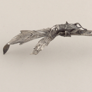 Handle in the form of a patinated field cricket on a leaf.