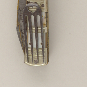 Folding knife with one large and two smaller blades, upper edge decorated with engraved inlaid brass. Large brass oval spoon bowl with pointed tip, engraved floral decoration on the back of spoon. Steel fork has four straight tines, heart-shaped openings on the joint and neck of the fork. Brass handle, inlaid with mother-of-pearl squares on front and back. Four brass rivets on each piece of mother-of-pearl.