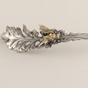Handle in the form of a gilded hornet on a deeply scalloped leaf.