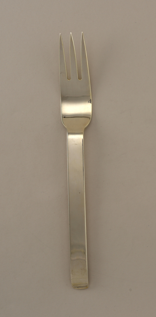 Integral piece. Three tines with long bowl, straight, flat handle, and rounded square terminal.
