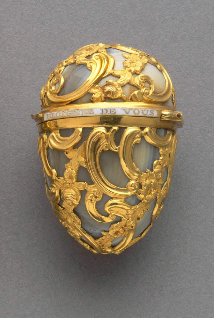 "Egg-shaped form of curving rococo gold cage work over gray agate. Hinged lid with white enameled band showing the phrase, ""Eloignez de vous rien n'est agreable"" (Separated from you nothing is pleasant)."