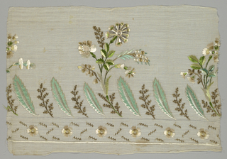 Part of a border, probably for a dress, with a main section composed of vertical lancet leaves alternating with a floral sprig. Every third sprig is the stem for a large exotic flower reaching up into the field. Narrow lower band a repeat of small rosettes and short bands. Colors are predominantly green, tan and brown on a natural linen ground.