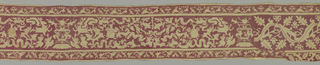 Very wide horizontal repeat with symmetrical central motive with heart pierced by arrows flanked by two lizards escaping from ring supported by leaf arabesques clasped by banderole with worn letters. Fantastic stylized animals, putti, flower and leaf forms, banderoles with Greek-like inscriptions in broad area on each side. Guard band top and bottom with single row of fantastic birds. Desgins are in linen on  ground of faded solid red silk long-legged cross-stitch. For short area at right end, central pattern changes to large-scale vine with leaves and flowers.