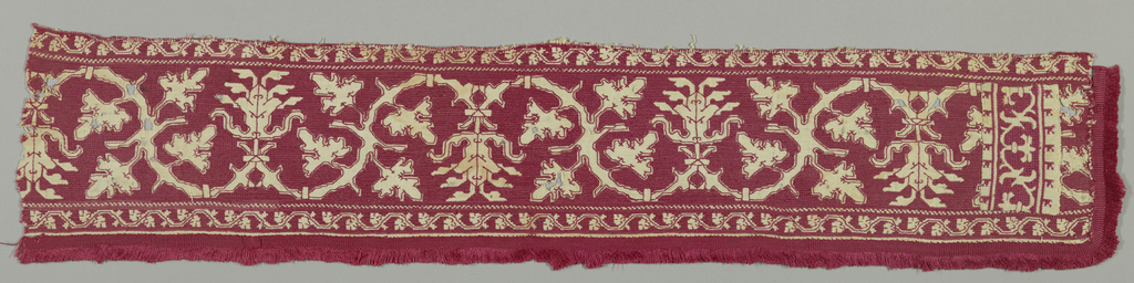 Band with attached fringe showing a symmetrical, curving vine. In red silk on linen ground.