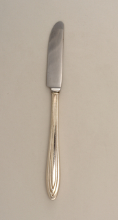 Small blade attached to elongated oval handle with molded pattern of four overlapping panels interlocked at handle.