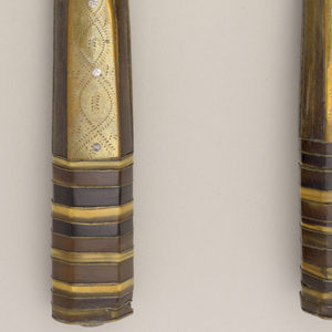 Wide steel blade, slightly up-curved lower edge, angled end, pointed. Tang with button end. Handle eight-sided. Brass scales on major plane engraved with wriggle work; four sides of bone; two exposed tang sides. Handle end with 24 laminated sections of tri-color horn and brass plates. Plain brass end.
