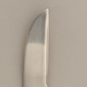 Pointed fish blade joining flaring outward handle.