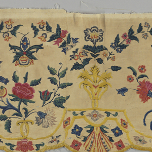 Narrow valance. Closely woven cotton (tabby weave) embroidered in polychrome wool. Design shows alternating clsuters of roses and carnations arranged under symmetrically curving floral branches. Lower edge scalloped. Colors, shades of red, rose, blue, violet, yellow, green. Stitches mostly chain and stem stitches.