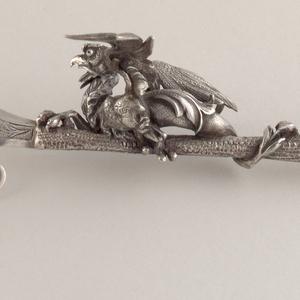 Modeled dragon figure on handle and engraved dragon on blade.