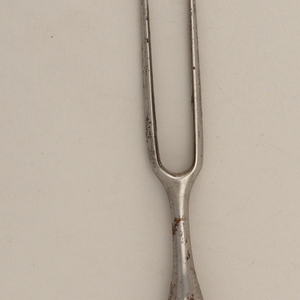 Two long curved tines, rounded shoulders and baluster-shaped neck. Silver ferrule has scalloped edge. Pistol-shaped white porcelain handle, decorated in relief with scrolls, acanthus leaves and flowers. Small cap on top of handle.
