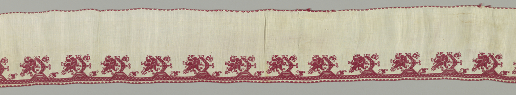 Long narrow border with a pattern of stylized plants at one edge in a row. In red silk on linen.