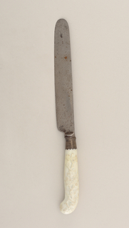 Straight-sided blade with rounded top, plain bolster. Silver ferrule with scalloped edges. Pistol-shaped, white porcelain handle decorated in relief with floral sprays.