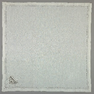 Cream-colored napkin or tea cloth embroidered with initials and ornamented with cutwork and lace.