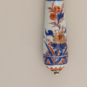 Sabre-shaped blade, silver ferrule with horizontal bands. Tapering porcelain handle, floral decoration in blue (underglaze), red and gold on a white ground. Silver button cap at the top of the handle.