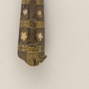 Two-tined fork, curved shoulders and baluster neck. Handle hexagonal in section; bone inlaid with circular motifs of mother-of-pearl and brass. Brass mounts decorated with circular motifs.