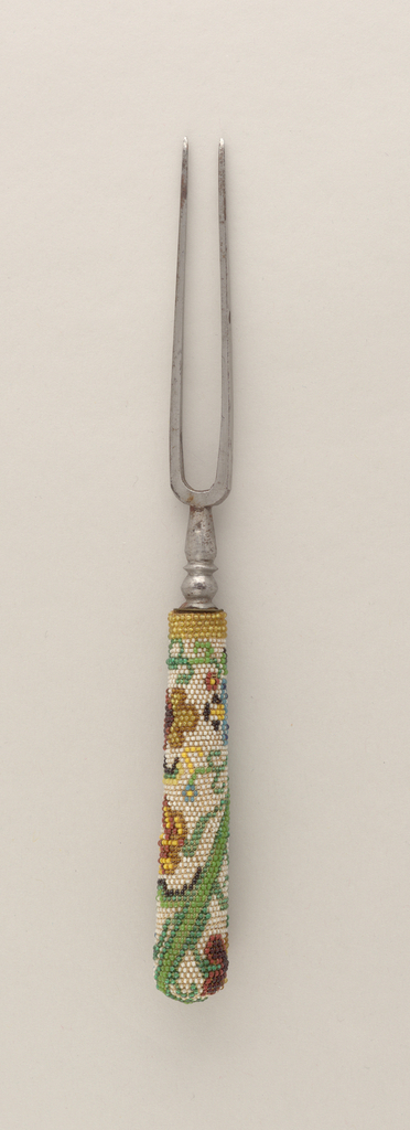 Two-tined fork with baluster neck. Tapered handle decorated with multi- colored glass beads; floral pattern in green, blue, brown and yellow on white ground.