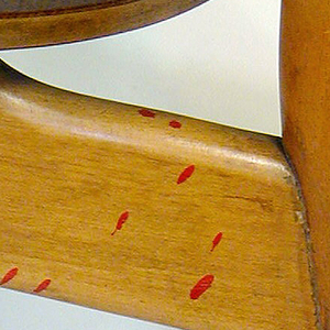 Chair with wide molded plywood back, round edged sides curving inward; seat is similar but smaller. Flaring straight legs with stretchers on all four sides.