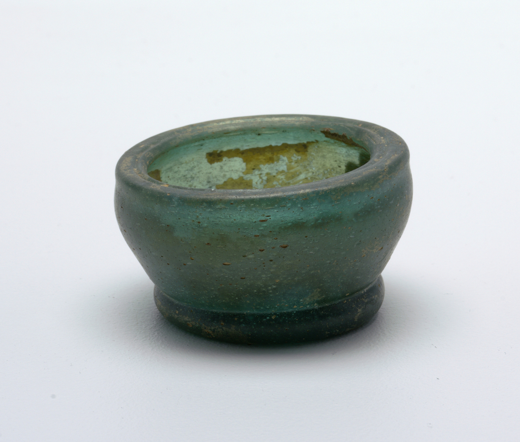 Thick glass.  Bell-shaped, with inturned lip and circular foot.  Traces of iridescence.  Dark Green glass