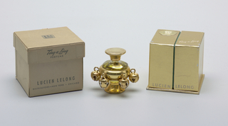 Squat round clear glass bottle on gold-toned circular foot; the form encased in gold-toned metal sleeve with six jingling bells around circumference; removable circular cap, also in gold.