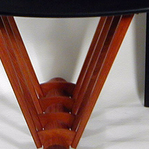 Chair with slightly curved back; back composed of a flat sheet of wood with square cut out at bottom that angles up to become seat. Back also has small sheet of curved wood that acts as support for back. Seat is supported by four V-shaped wooden bars that radiate from a cylindrical wood bar on the ground.
