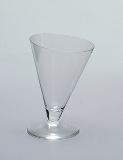Short cone-shaped glass at an asymmetrical tilt to glass