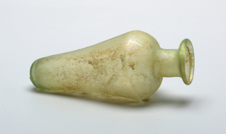 fragment of yellow green glass A) Elongated body tapering off, toward rounded bottom. Neck rising from body and terminating  in irregularly rounded lip. Pontil [?] mark on bottom. B) Medal stand with three curved legs.