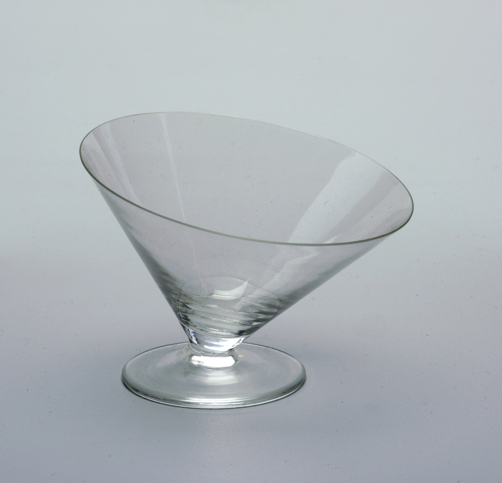 Short and wide cone-shaped glass at an asymmetrical tilt to glass, sherbert or martini