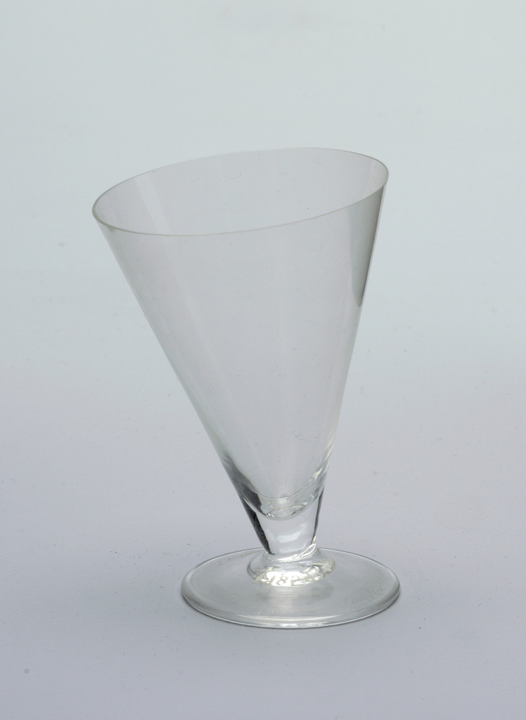 Short cone-shaped glass at an asymmetrical tilt to circular foot.