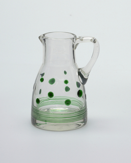 Clear glass pitcher cylindrical neck flairing to with green decoration of dots above band of thread like trails; etched on one side of neck: 6/20 L; loop handle on one side, from neck to mid-body