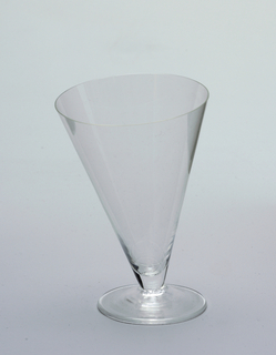 Cone-shaped water glass at an asymmetrical tilt to glass