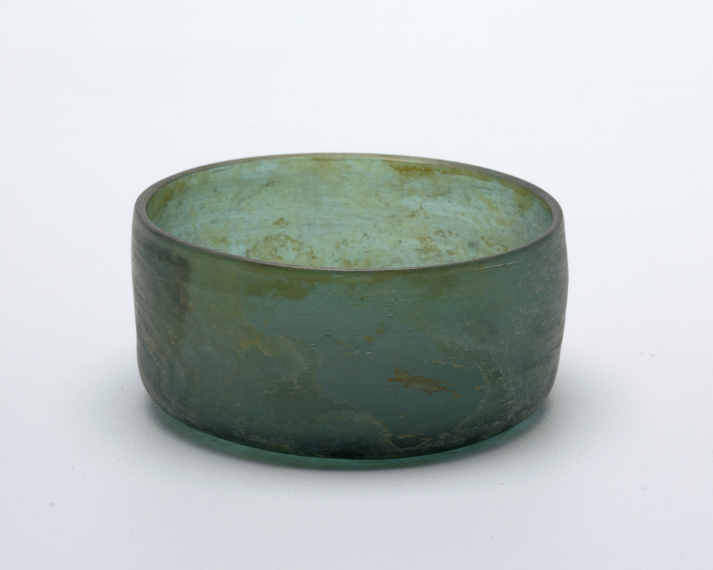 Deep circular bowl with straight sides tapering slightly at the rim.  Under-side concave.  Resonant.  Slightly incrusted.  Dark green glass.