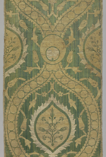 A length of woven velvet with a large-scale, vertically symmetrical design in the style of the seventeenth century. Ogees with serrated edges containing small flowering tree motifs are surrounded by a large-scale ogival framing devide made up of pearl borders; with a pearl crescent at the point of intersection. In gold metallic twill on a ground of green silk velvet pile in various shades, giving a striae effect.
