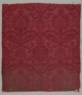 Scrolling pattern of leaves and cartouches in red damask.