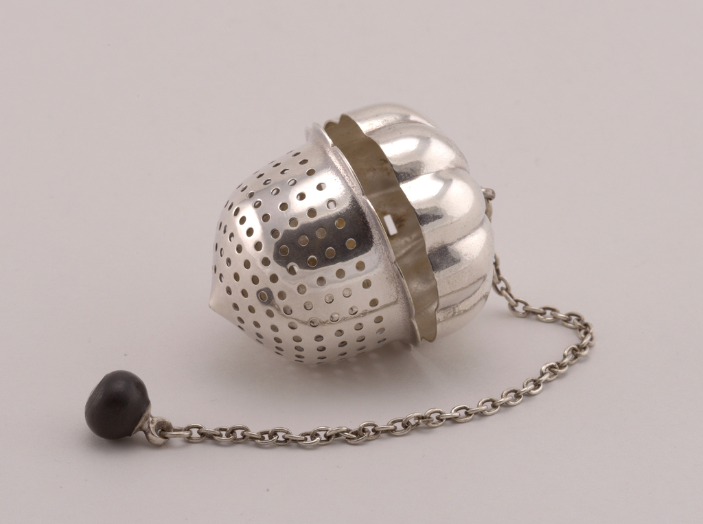 Acorn-shaped with hinged, gadrooned top lid and small strap handle joining lid with perforated bottom half, pointed end with scalloped rim. Suspension ring, chain, and knob attached to lid.