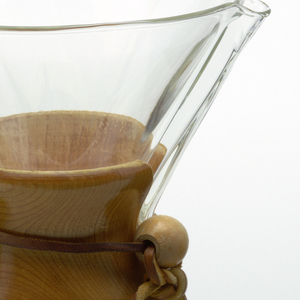 Large hourglass-shaped coffee maker of transparent glass with high neck and circular mouth molded with a narrow spout; tapered wood collar/hand grip at neck tied with leather thong with bead stop; small projecting dot as water level indicator in lower body, vertically aligned with spout.