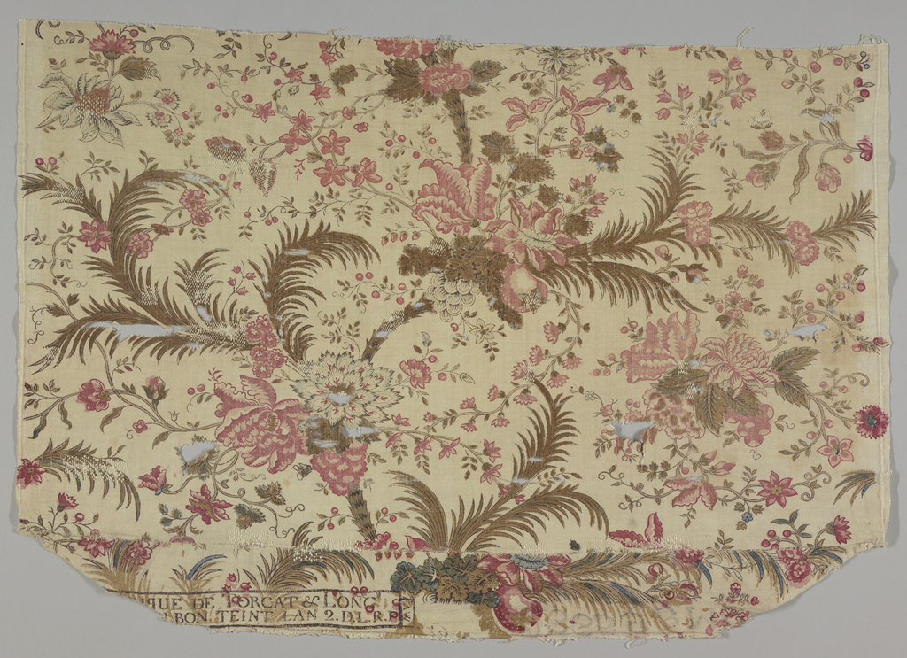 Exotic flowers and palm trees in black, two reds, blue and dull yellow. From the shape it appears that this fabric was used as upholstery on a chair.