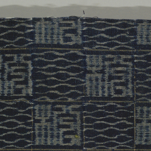 """Textile with checkerboard desing of two alternating geometric patterns created in the weft ikat or kasuri technique. Pattern described as """"seal script."""""""