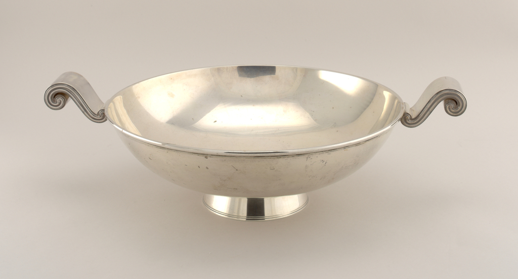 """Circular shallow bowl on circular foot. Foot straight-sided, tapering toward bowl. Applied rim on bowl. Plain mirror polished interior. Two """"S"""" scroll handles at sides; each broad and flat on upper surface, with reeded pattern at sides."""