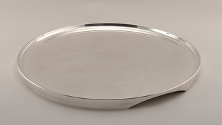 Shiny silver-plated metal circular tray with a raised rim.